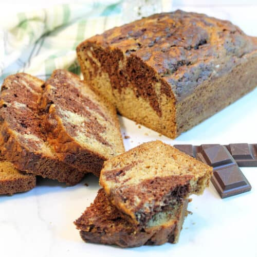 Halved piece of banana bread in front of sliced loaf with chocolate on side.