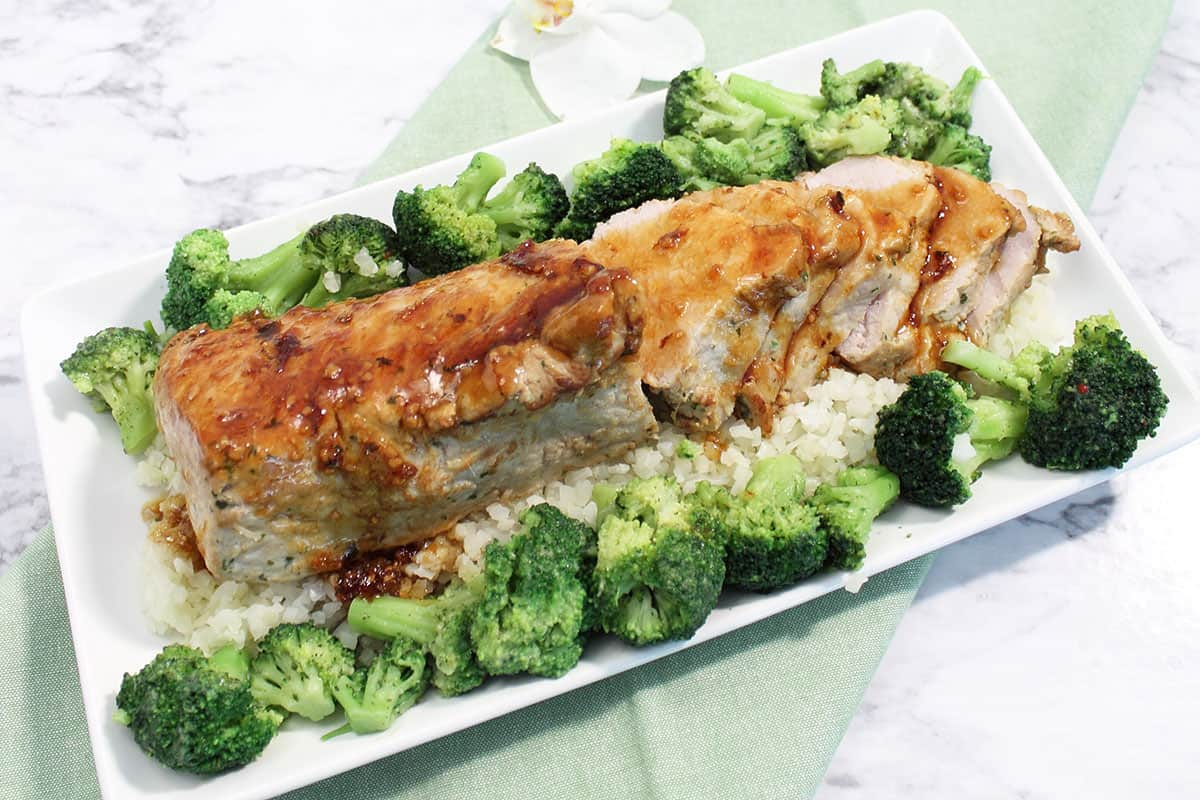 Overhead of pork loin on white serving plate with broccoli.