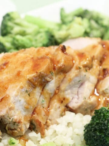 Sliced pork tenderloin on white serving plate with gravy.
