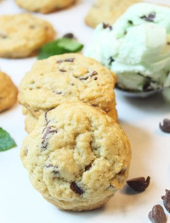 Stack of cookies with other cookies and chips scattered around with scoop of ice cream.