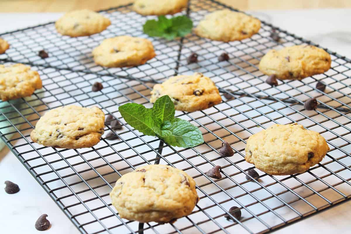 Mint chip cookies cooling on wire rack with mint sprigs and chocolate chips scattered around.