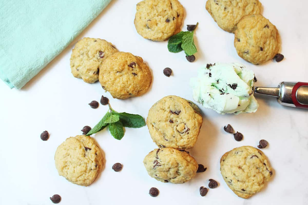 Scattered cookies among mint leaves chocolaet chips and scoop of ice cream.