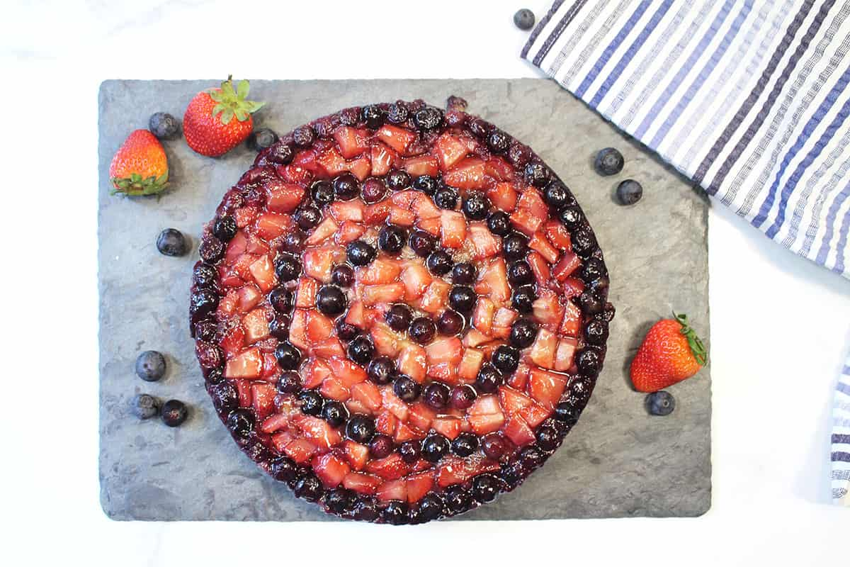 Cake turned out of pan with fruit on top.