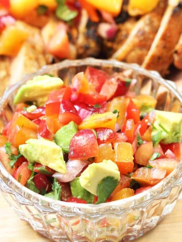 Closeup of salsa with avocado in glass bowl with pork in background.