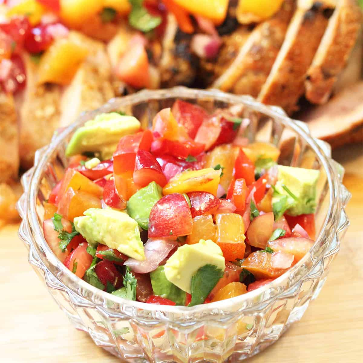 Closeup of peach cherry salsa tossed with avocado in glass bowl with pork in background.