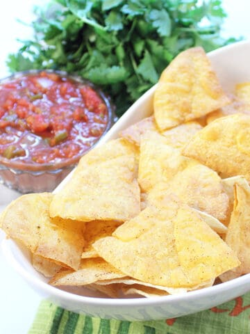 Closeup of tortilla chips in white bowl beside salsa and cilantro.