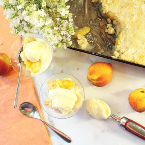 Overhead of 2 servings next to peach napkin with peaches and scoop of ice cream next to it.