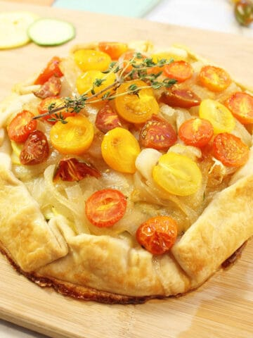 Closeup of browned squash galette on wooden board with thyme garnish on top.