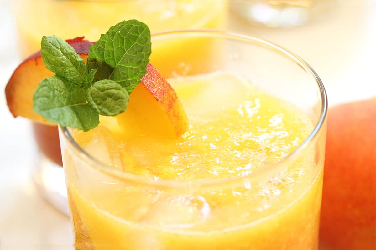 Closeup of top of glass filled with peach drink and garnished with peach slice and mint.