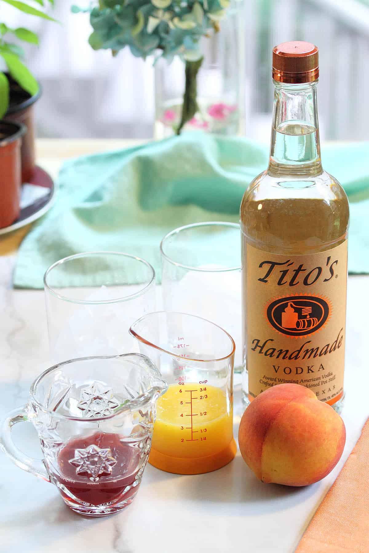 Ingredients vodka, peach, orange juice, cranberry juice on white table.