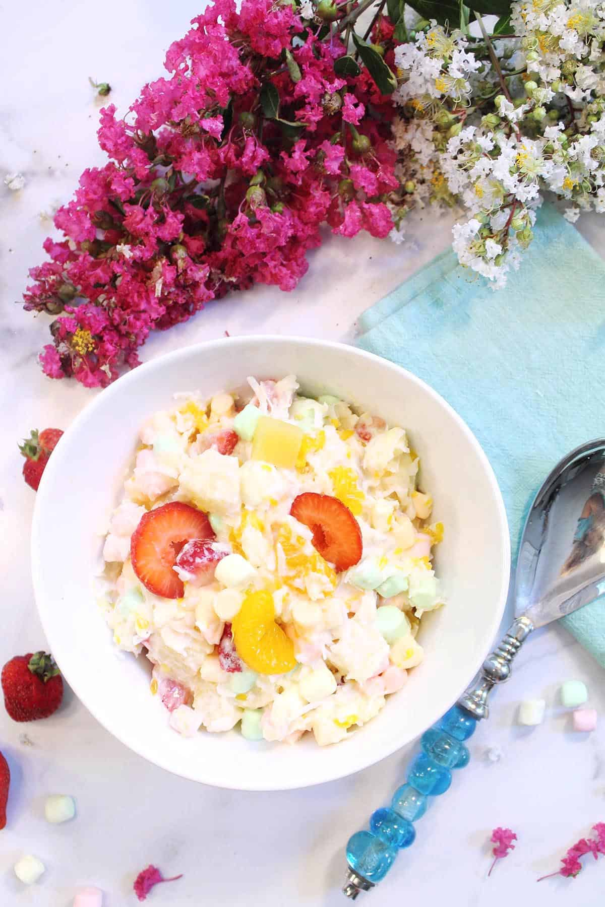 Overhead of white bowl of ambrosia salad covered with yogurt with serving spoon, green napkin & flowers on side.