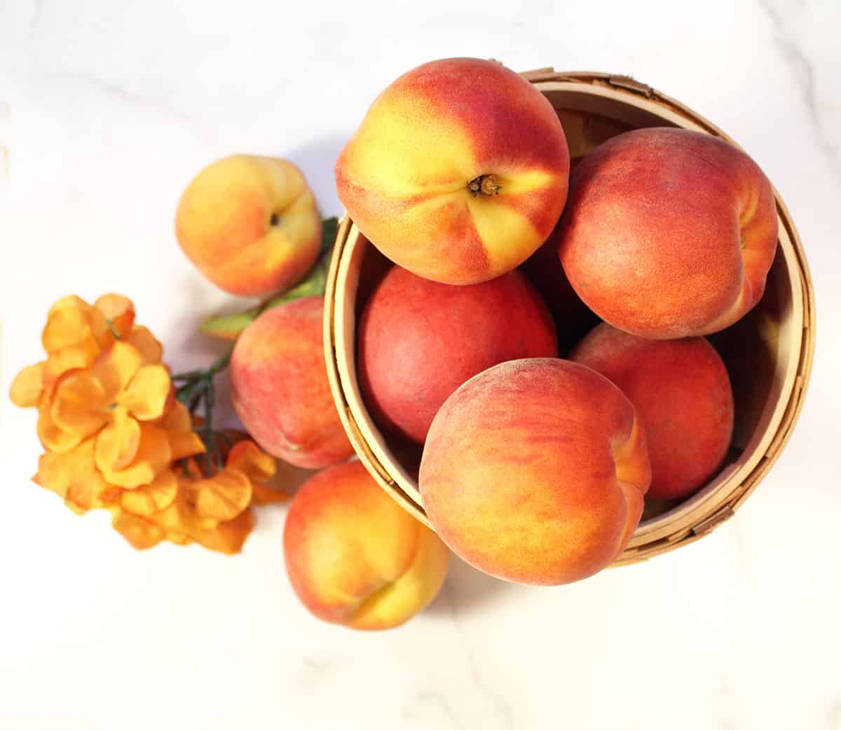 Peaches in a basket on white marble table.