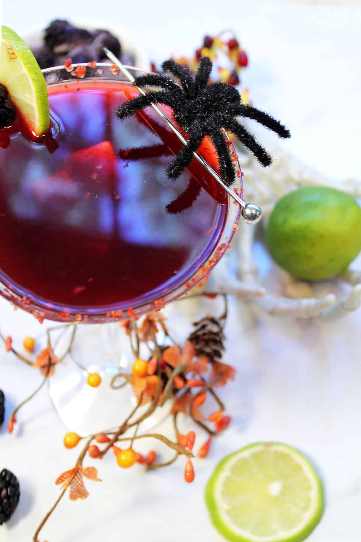 Looking into glass with lime and blackberry garnish and a lil ole spider.