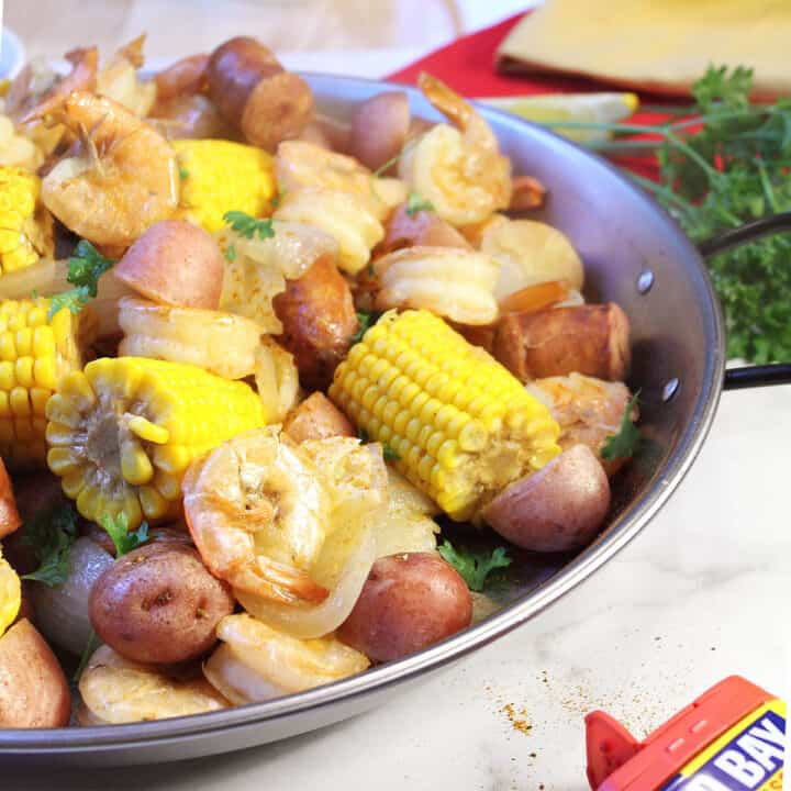 Partial view of low country boil in round pan with parsley.