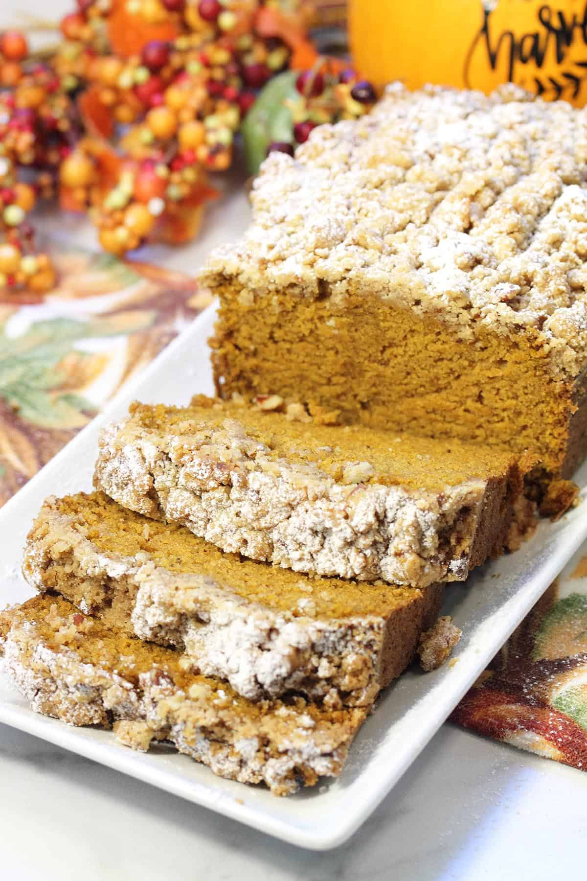 Sliced maple pumpkin bread with closeup of front slices on white platter.