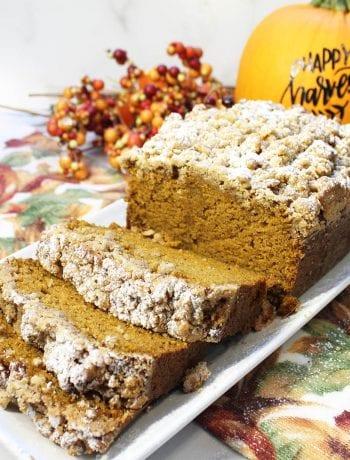 Sliced pumpkin bread on white platter with pumpkin in background.