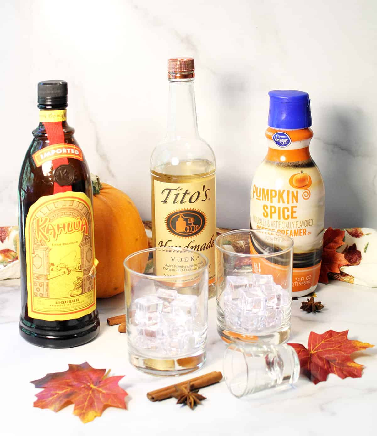 Autumn White Russian ingredients on white table with fall leaves.