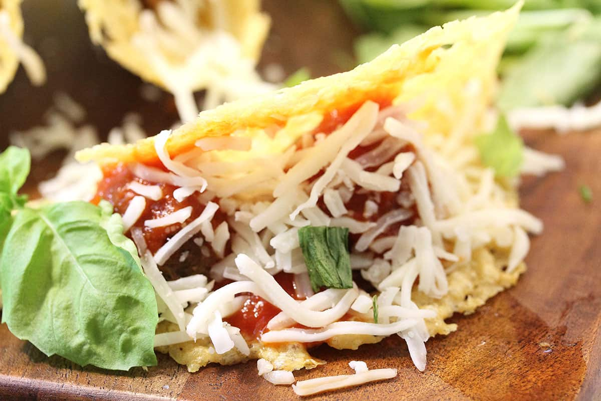 Closeup of inside of taco lying on its side on wooden board.
