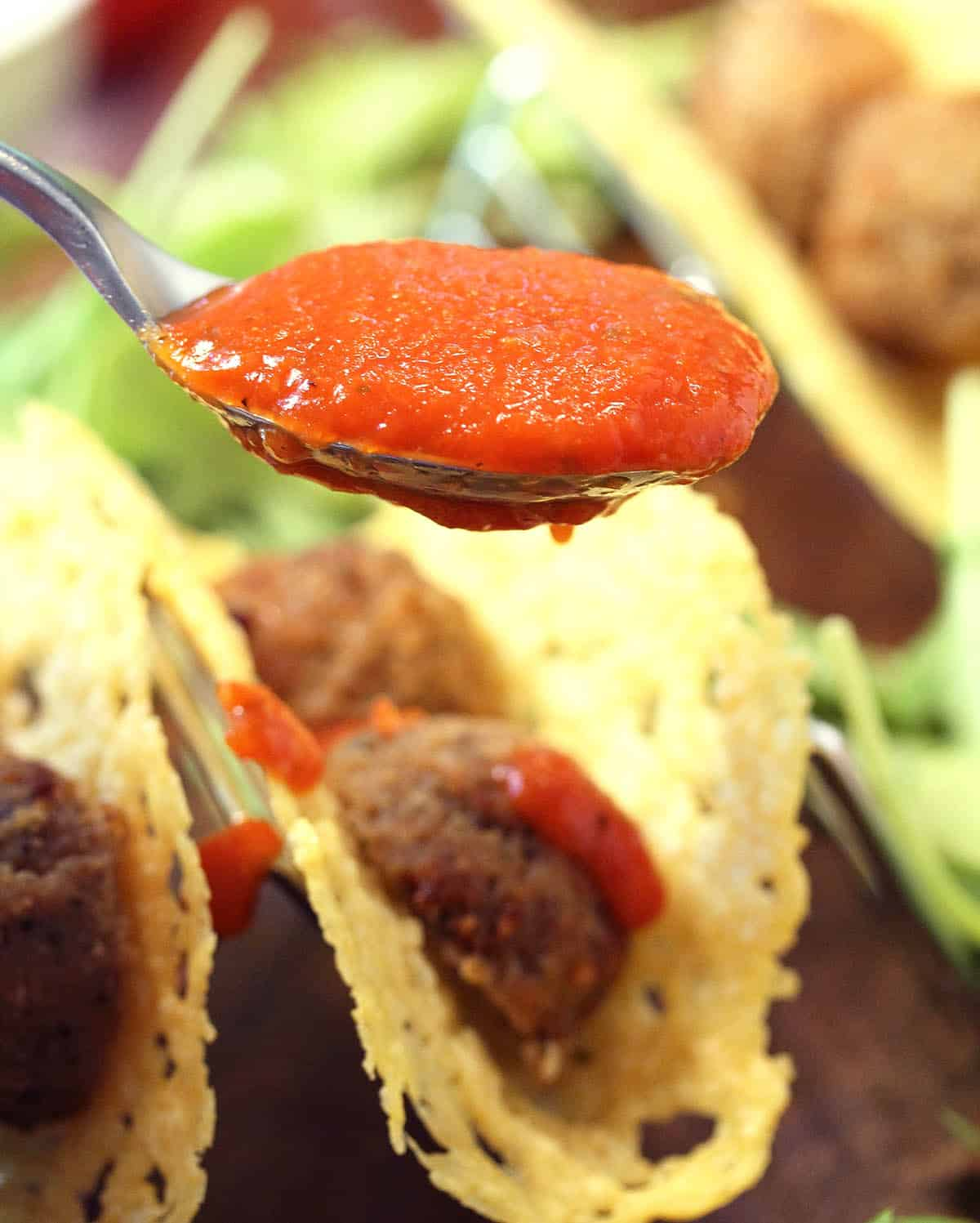 Closeup spoonful of Prego sauce over meatball tacos.
