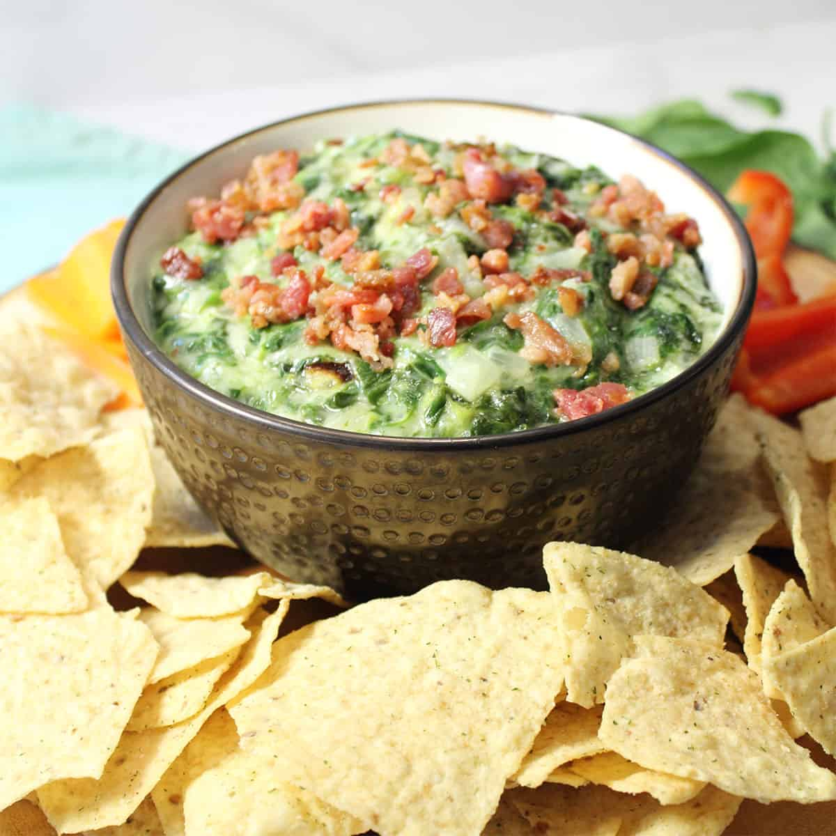 Dip in brown bowl on wooden circle with tortilla chips and dippers around it.