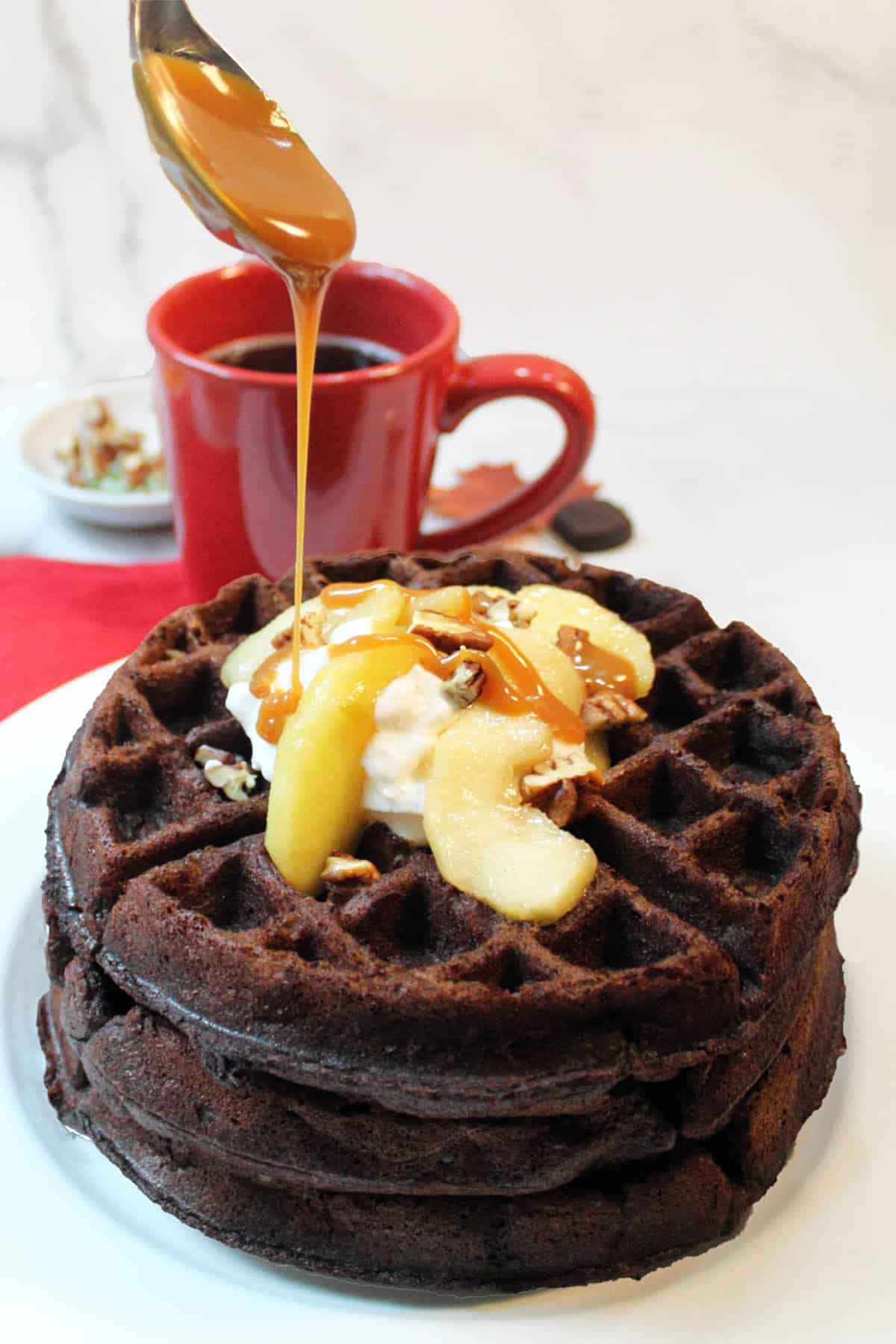 Drizzling caramel sauce over waffles.