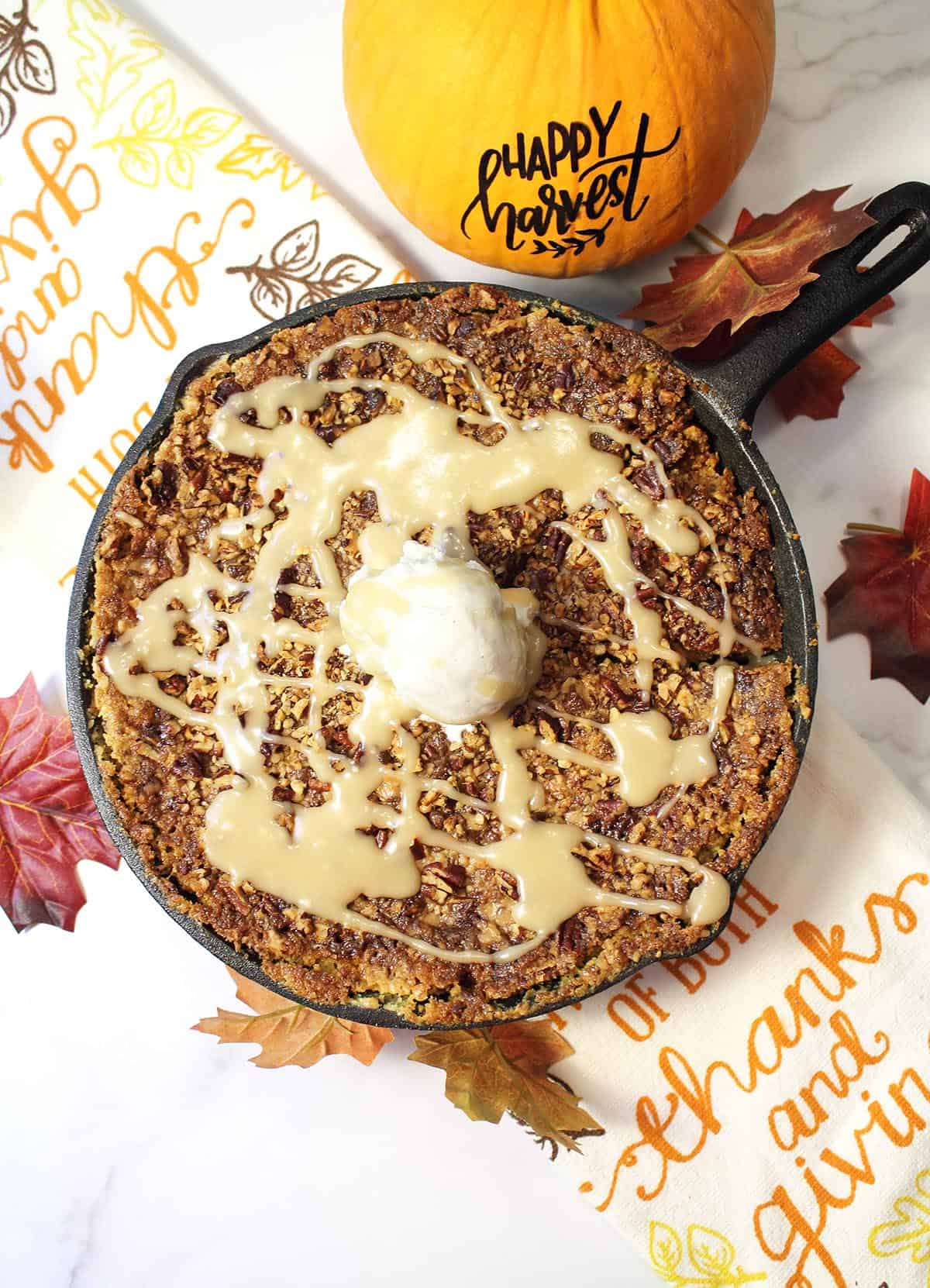 Overhead of baked pumpkin cobbler with scoop of ice cream on top and drizzle of maple sauce.