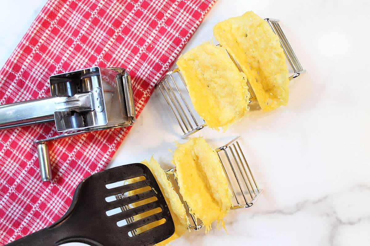 Forming taco shells by pushing into taco holder with spatula.