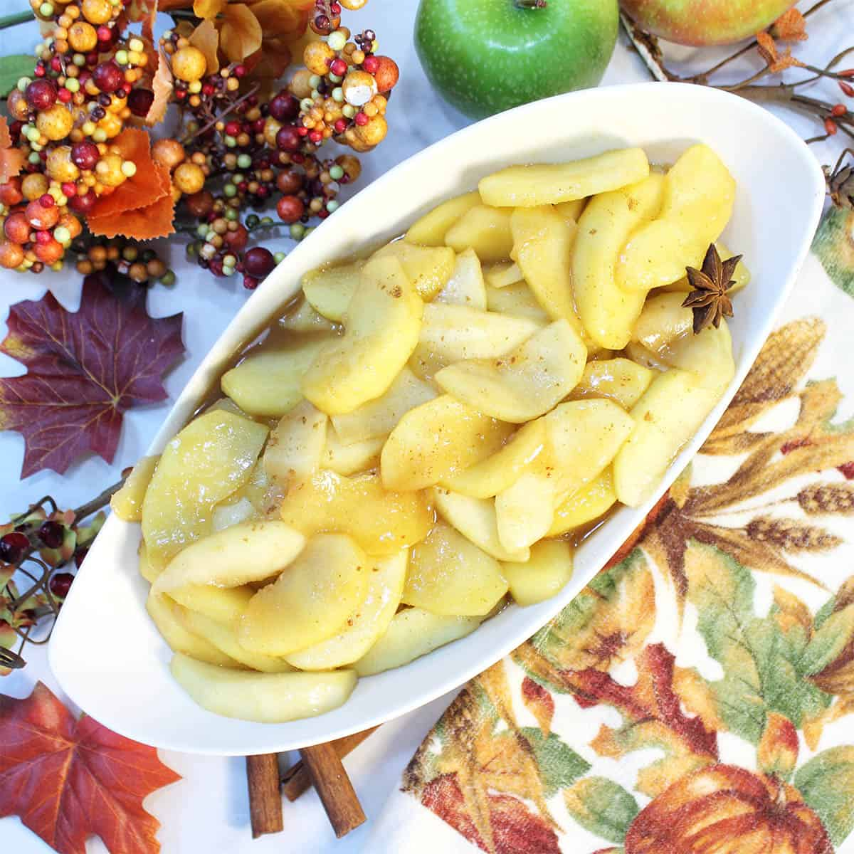 Overhead of serving bowl of apples with fall towel and leaves beside it.