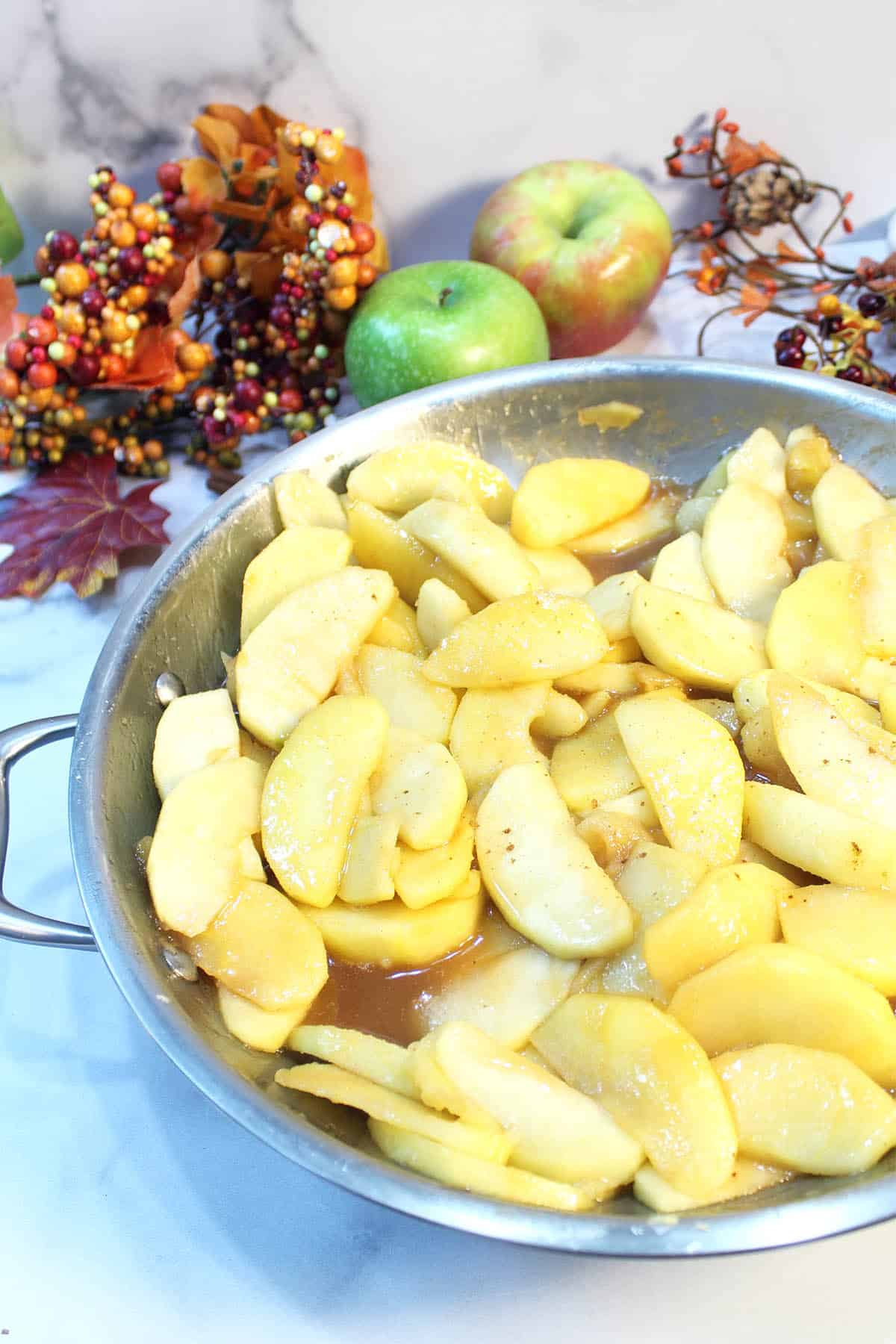 Partial view of skillet with cooked apples with fall foliage in back.