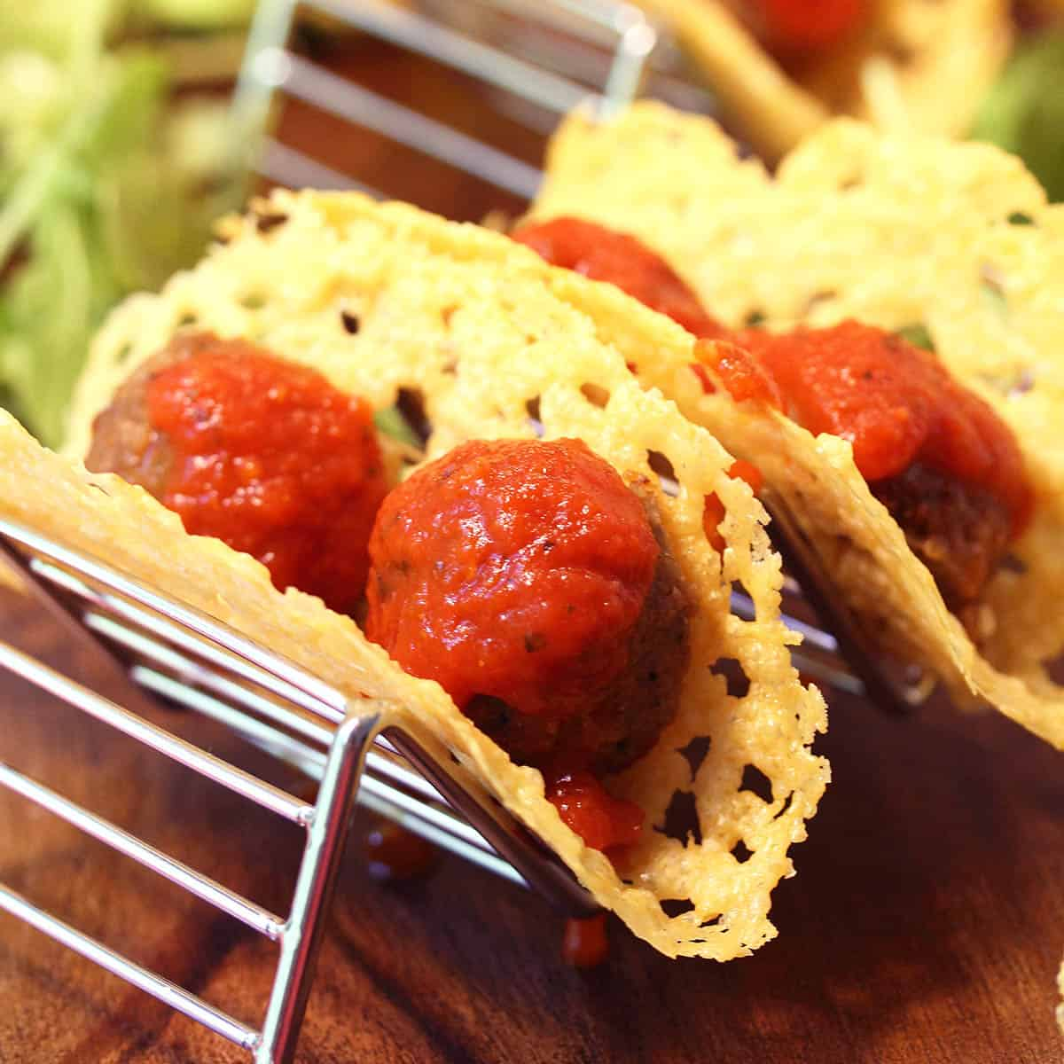 Sauce covered meatballs in cheese shells on taco stand.
