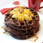 Stack of waffles on white plate with sauteed apples and caramel sauce over top.