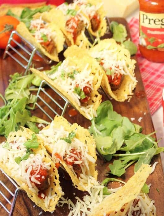 Tacos served in taco stands on wooden board with Prego sauce in background.