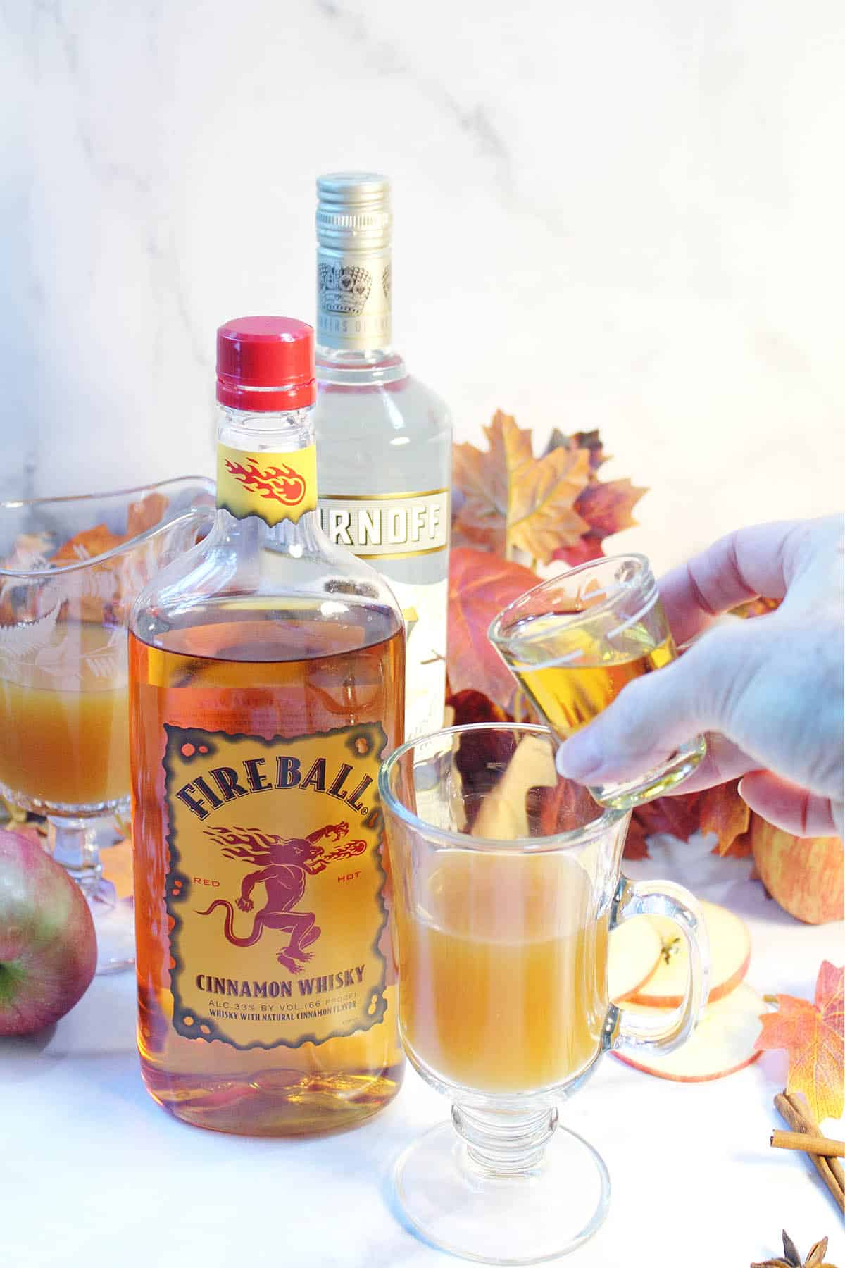 Adding fireball to cider with bottle next to it.