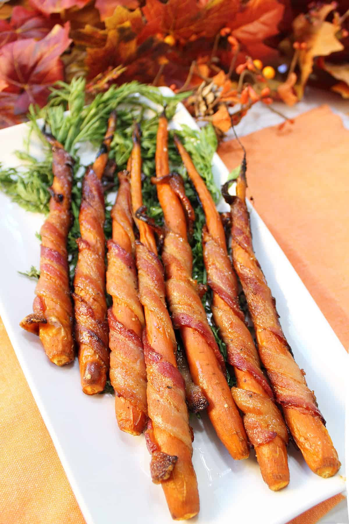 Bacon wrapped carrots on white platter with fall leaves in back.