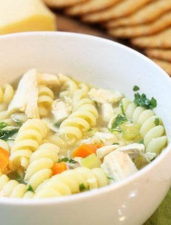 Bowl of chicken noodle soup in front of cheese tray.