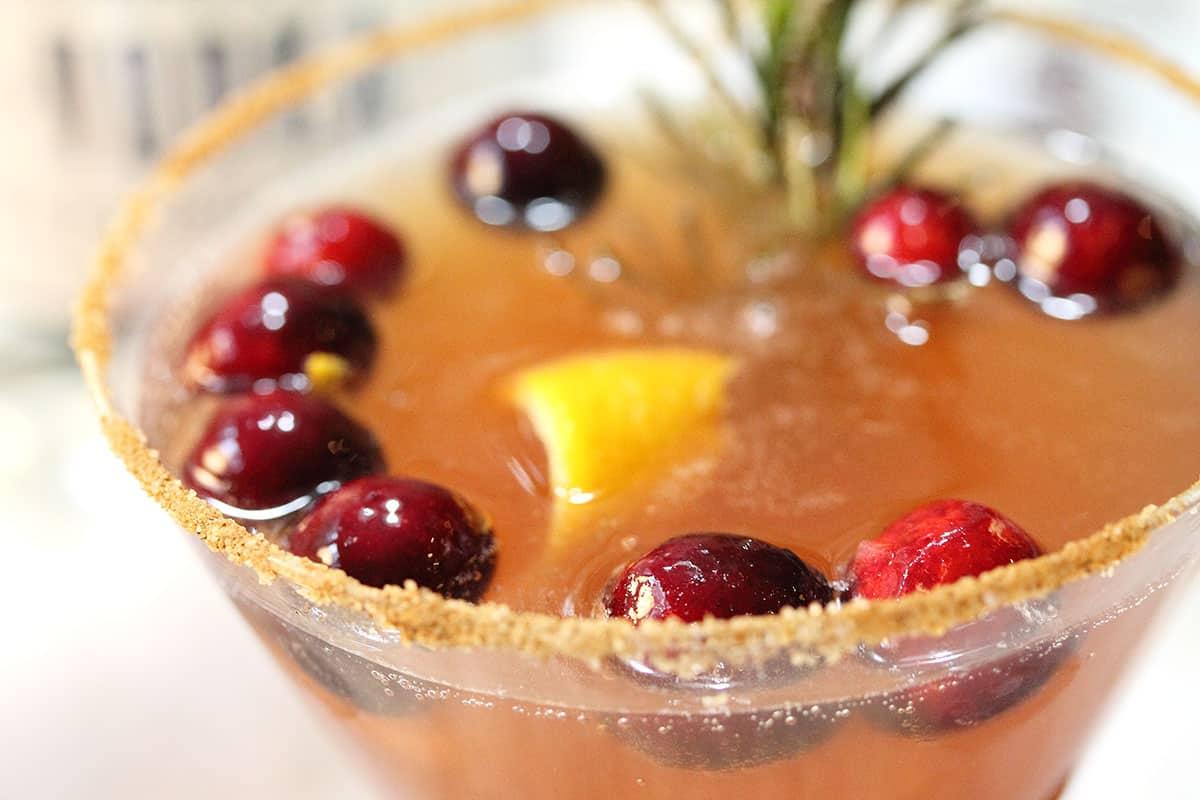 Closeup of cinnamon sugar rim and cranberries in cocktail.