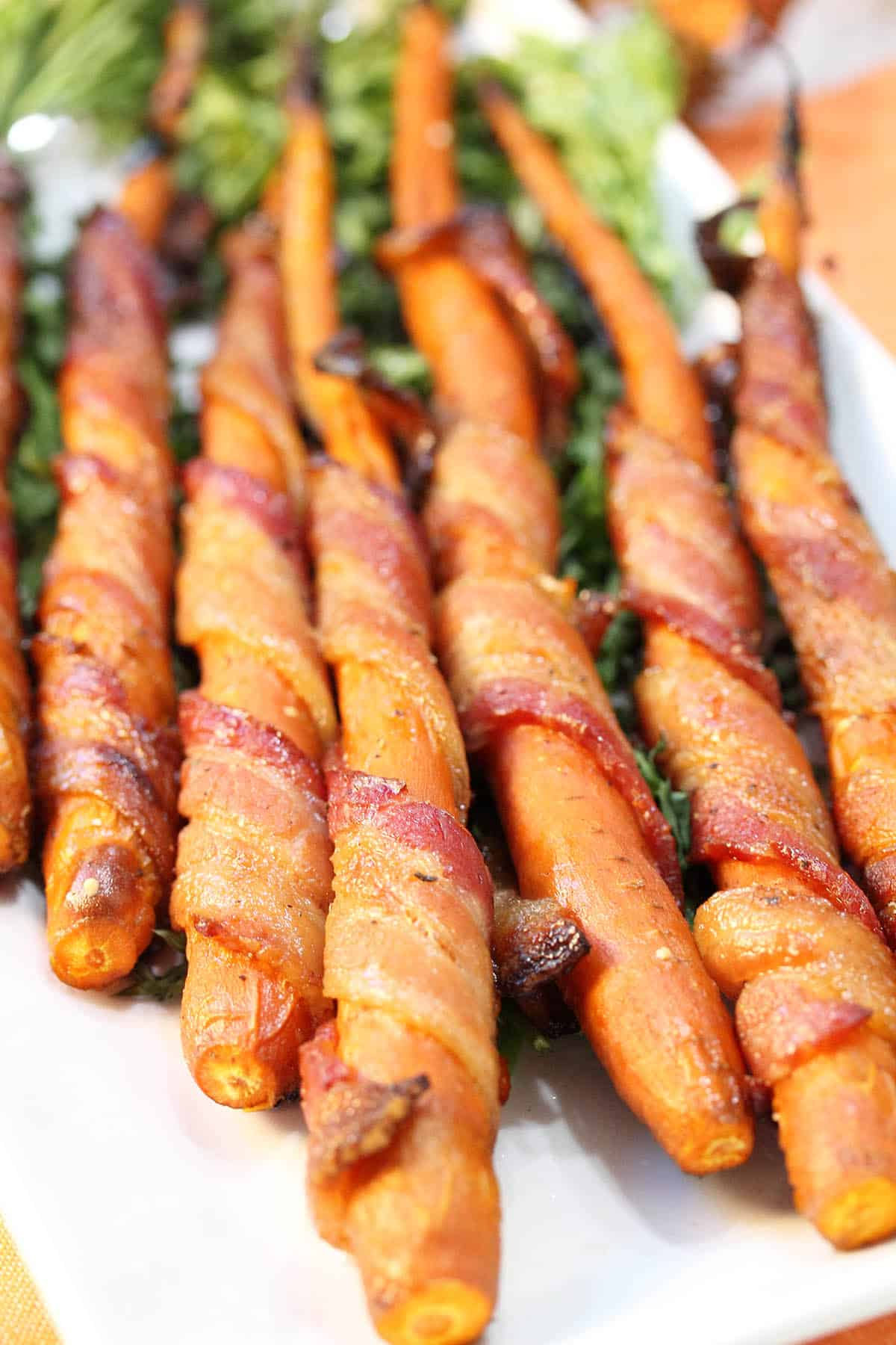 Closeup of cooked maple glazed carrots showing crispy bacon.