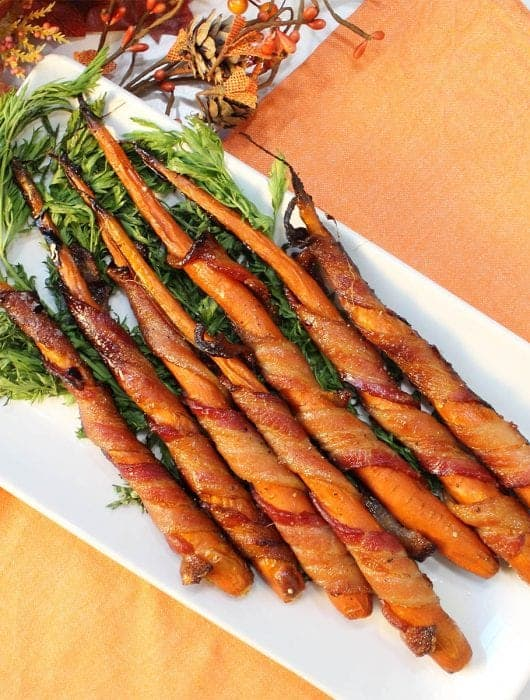 Bacon Wrapped Carrots on white platter with carrot greens on orange napkin.