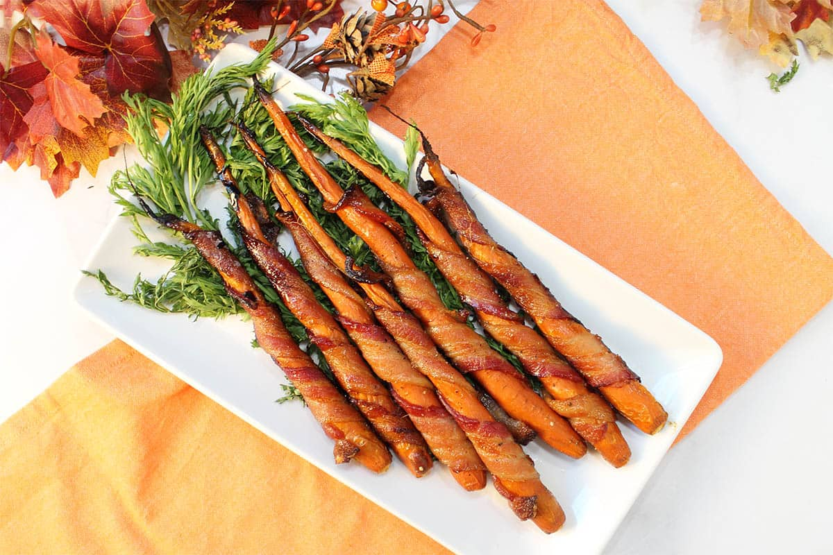 Maple Bacon Wrapped Carrots on white platter with carrot greens on orange napkin.