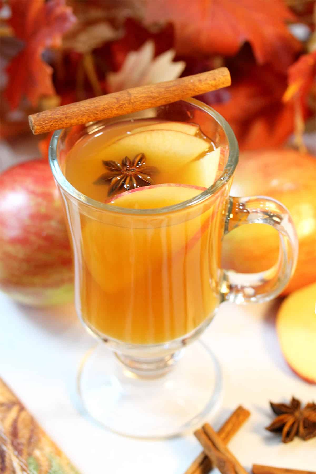 Mug of warm cider with apples and fall leaves in background.