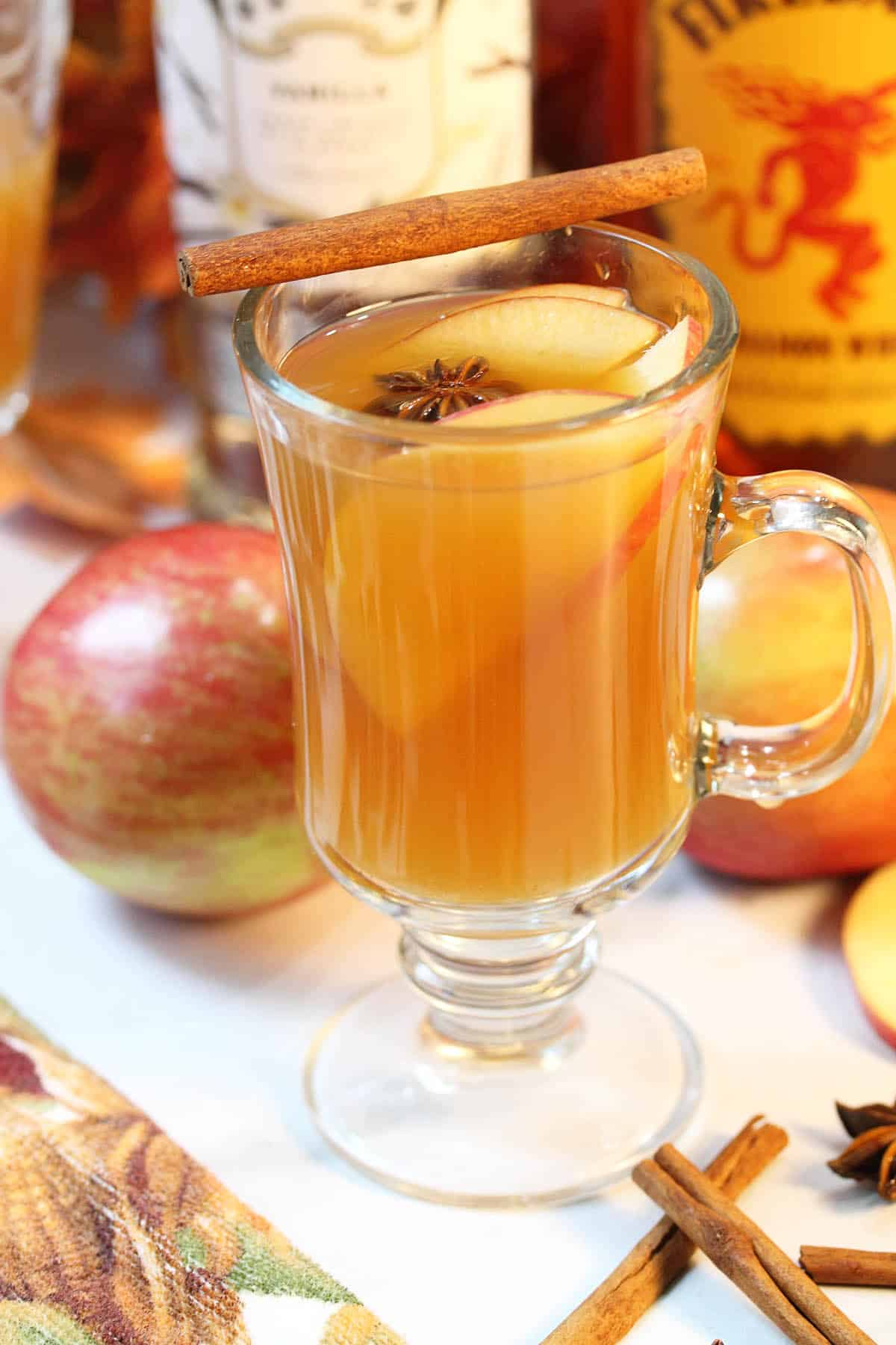 Mug of warm cider with apples and liquor in background.