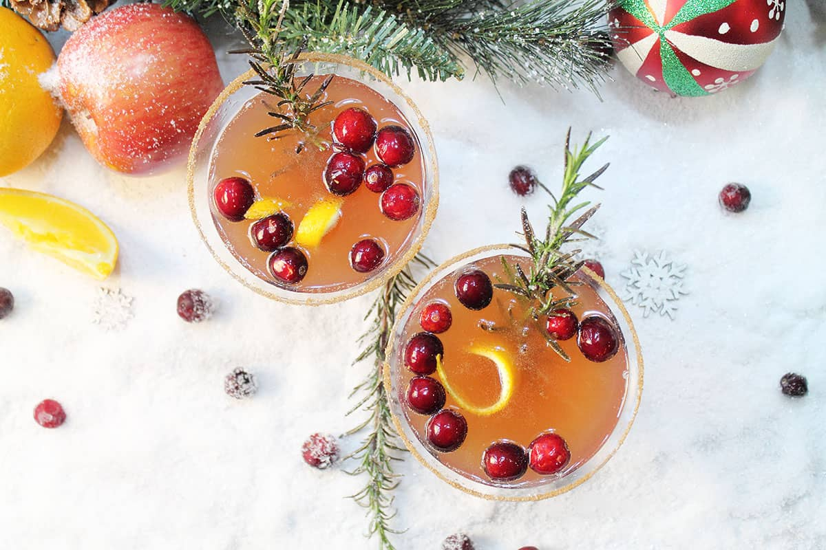 Overhead of vodka apple cider cocktails on snow with orange apple and ornament around them.