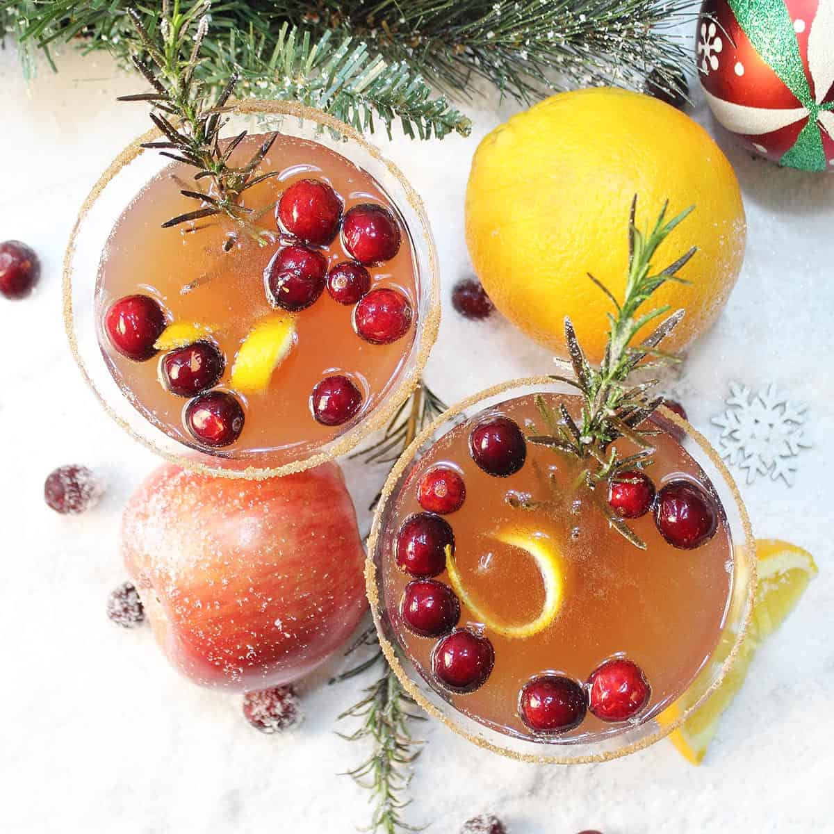 Overhead of cocktails on snow with orange apple and ornament around them.