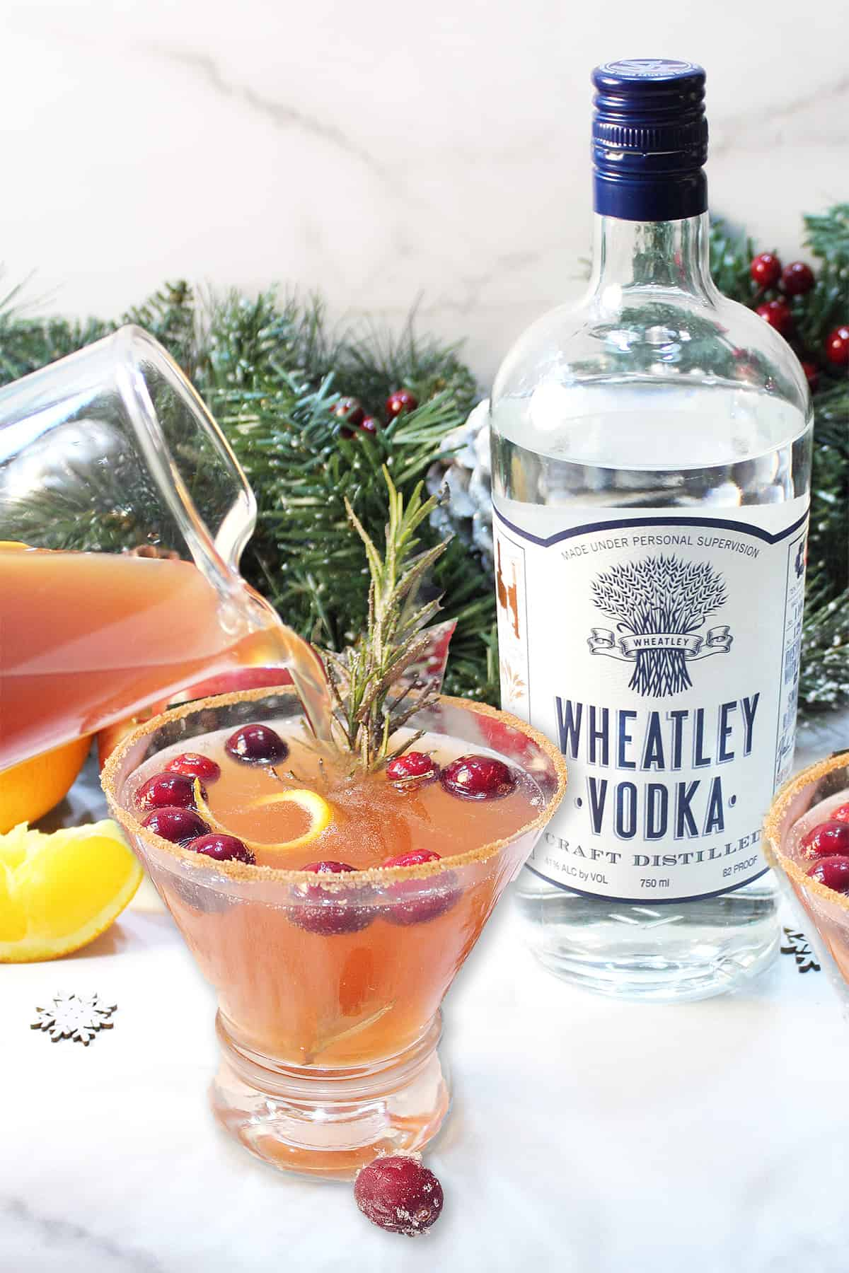 Pouring vodka cranberry cocktail into cinnamon sugar rimmed glass with Wheatley vodka bottle in back.