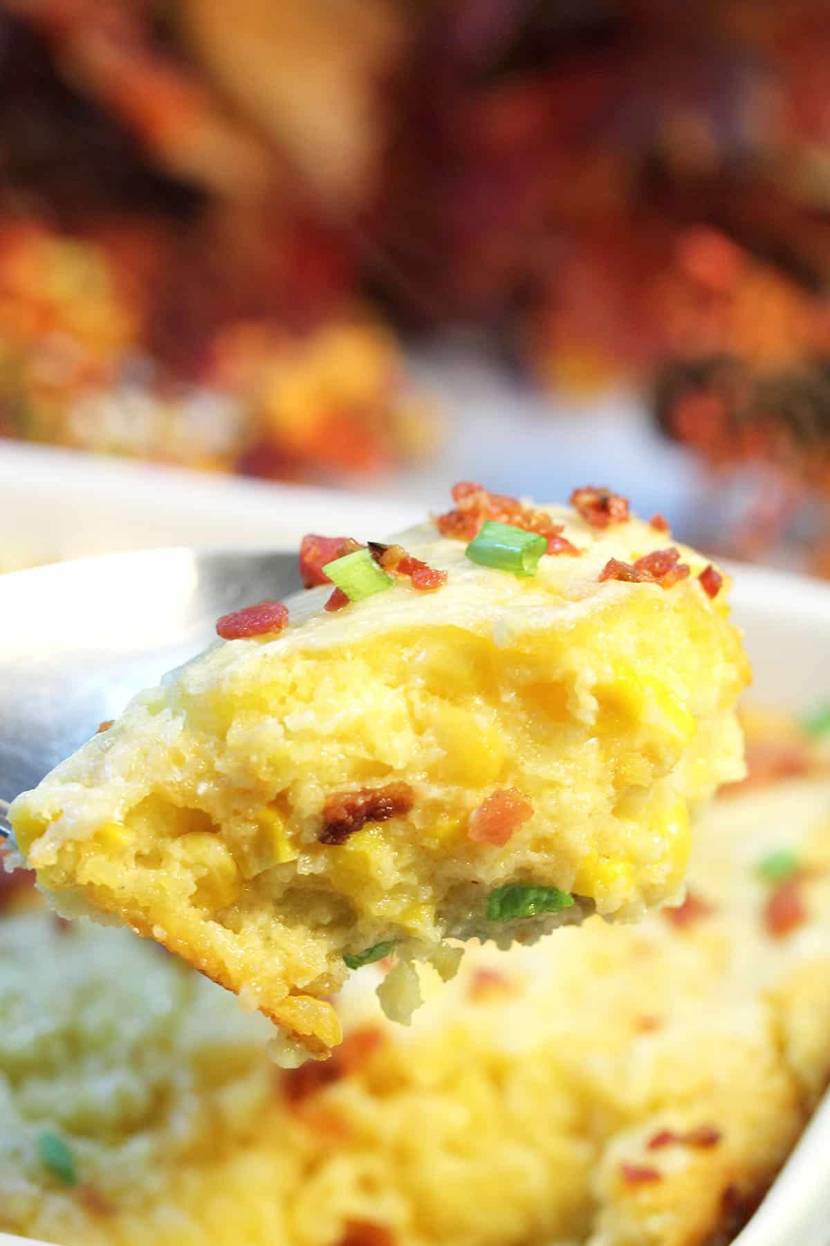 Spoonful of cheesy corn pudding over casserole.
