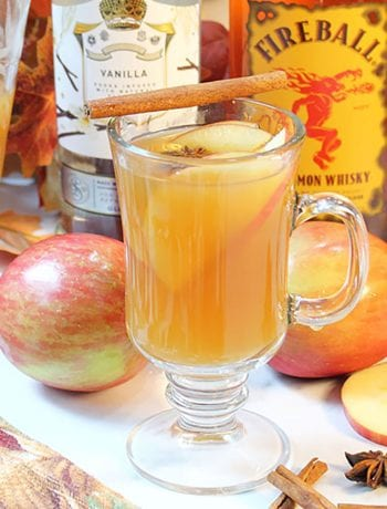 Warm apple cider cocktail with apples and liquor behind it.