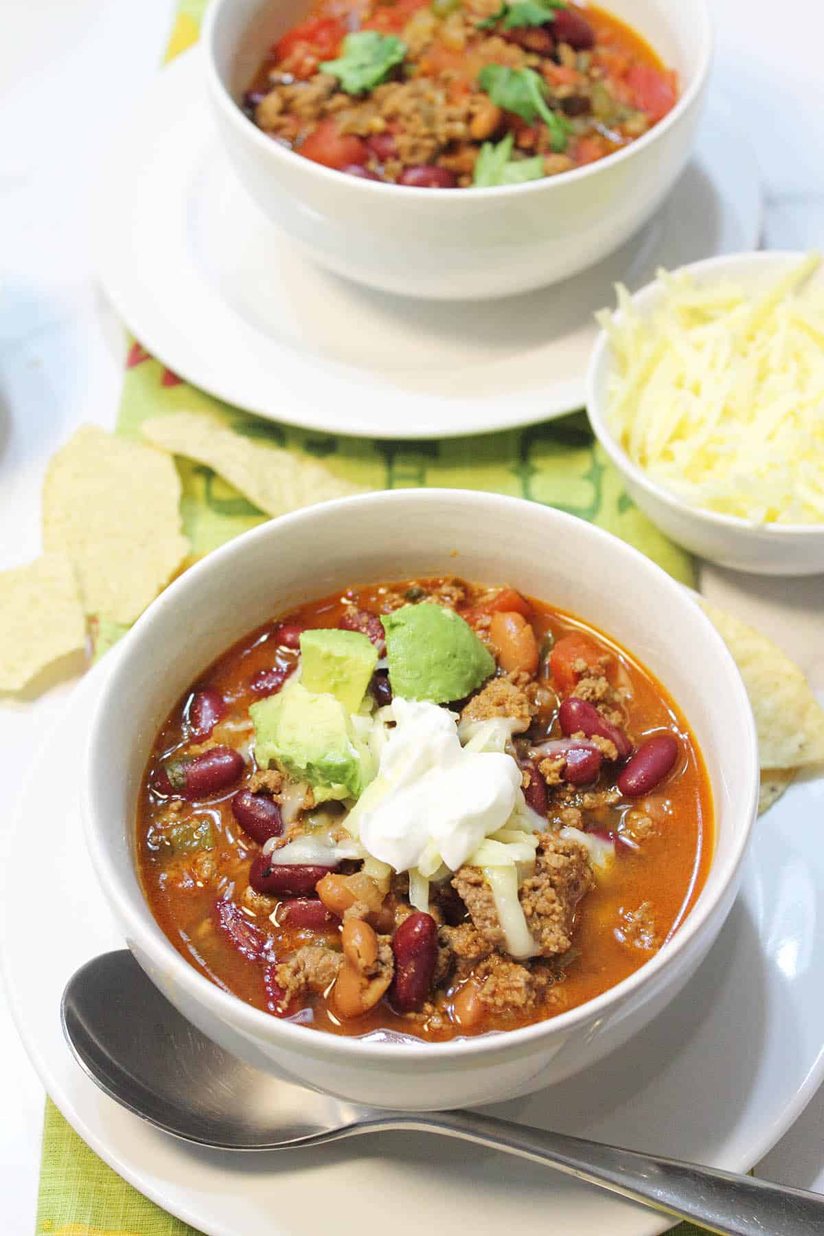 Two bowls of slow cooker Mexican chili on white table garnished with sour cream.