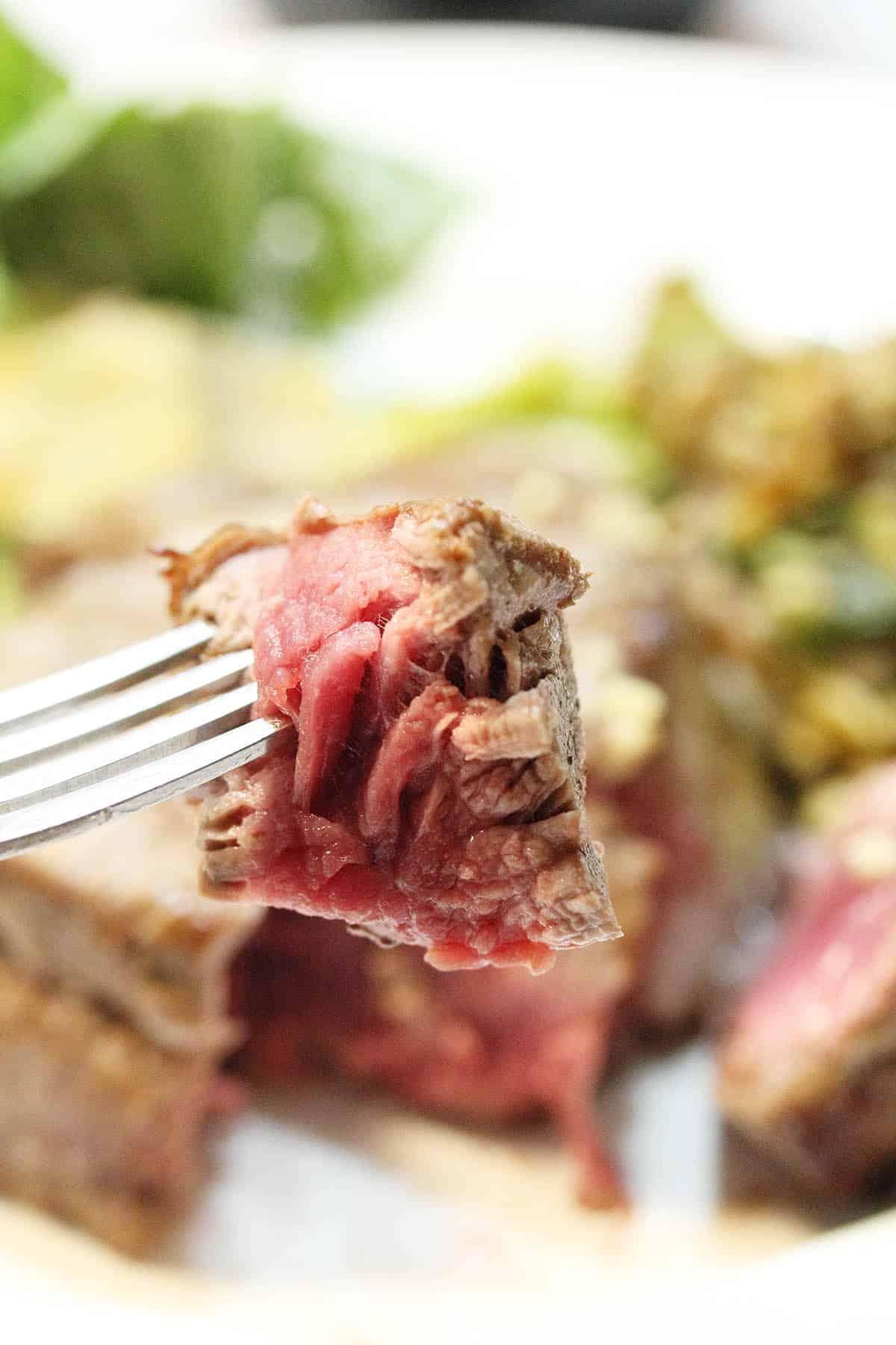 Bite of medium rare steak on fork over plate.