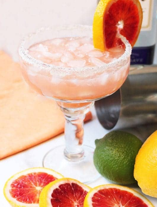 Blood Orange Margarita with blood orange and lime on white table