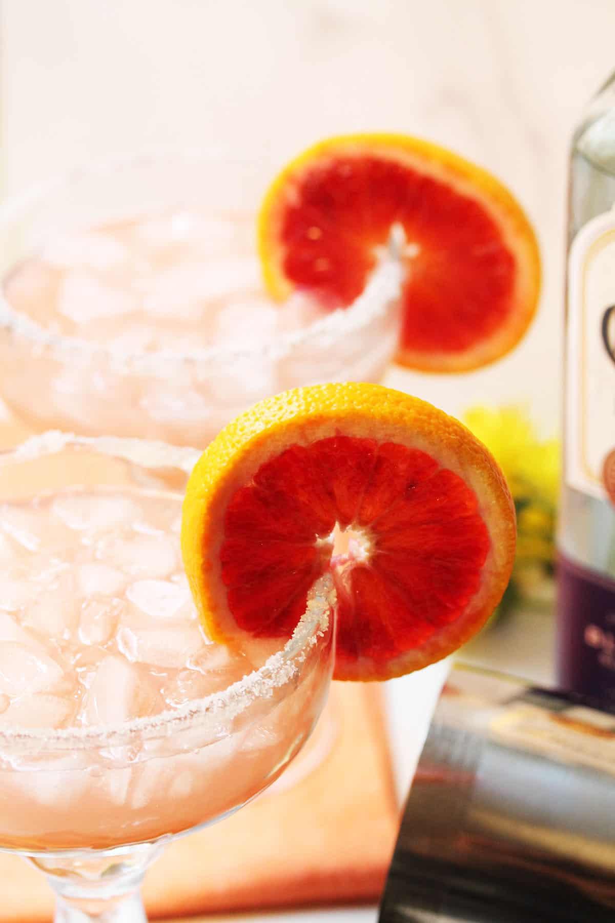 Closeup of partial top of cocktail glasses showing sugar rim and blood orange slice garnish.